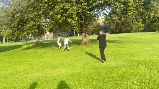 Young people playing football in the park
